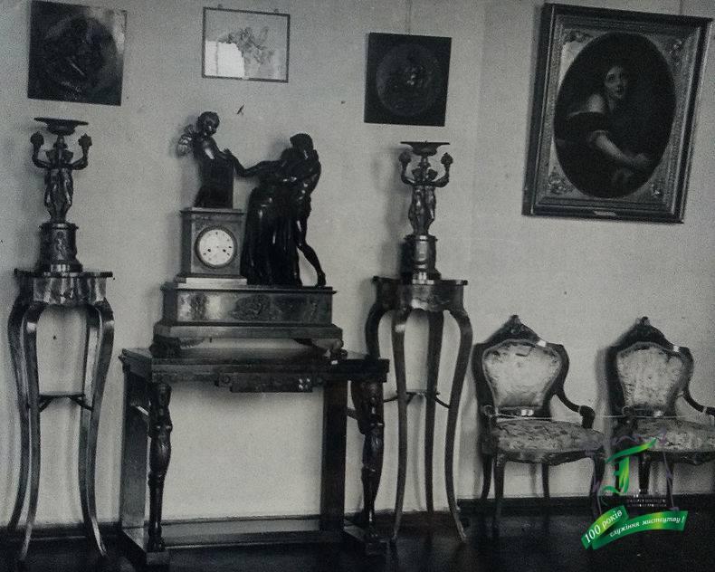 """Куточок експозиції з годинником """"Клятва Амуру"""" роботи П.Ф.Томіра (1751-1843). Фото кінця 1930-х рр."""